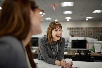 Two women seated in an office talking.