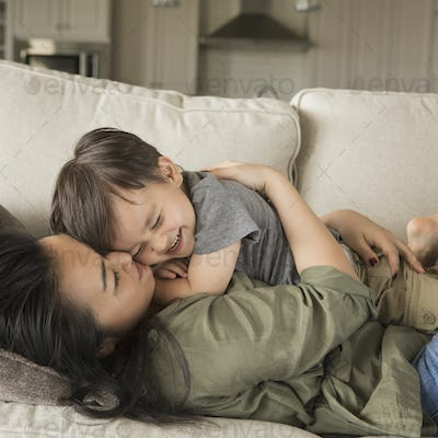 A woman lying on a sofa, smiling, cuddling her young son.