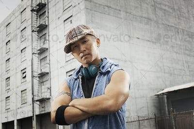 A young person in a denim sleeveless shirt, arms folded looking at the camera.