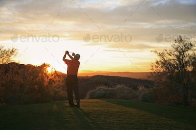 Golfer teeing off into the sunset on the golf course.