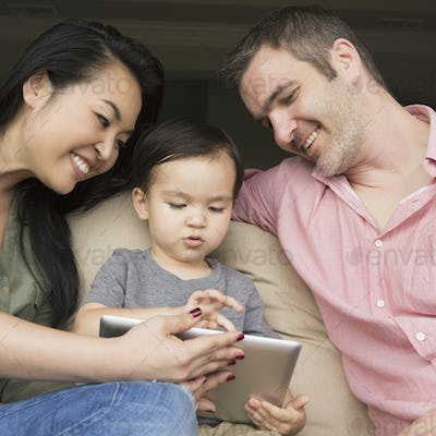 Parents sitting on a sofa with their young son, looking at a digital tablet.