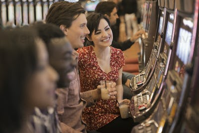A group of people playing the slot machines in a casino.
