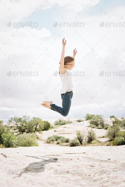 Barefoot woman wearing jeans, jumping up in the air