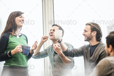 Four work colleagues on a break, laughing and raising their coffee cups.