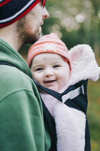 A baby in a sling being carried by her father, outdoors in winter.