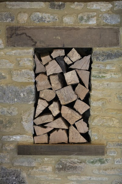 Fire wood stacked in a niche in a stone wall.