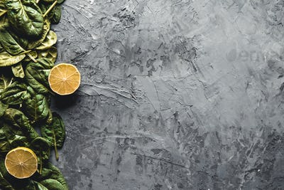 Spinach with lemon on a dark gray background. Wholesome food, vegan, eco products