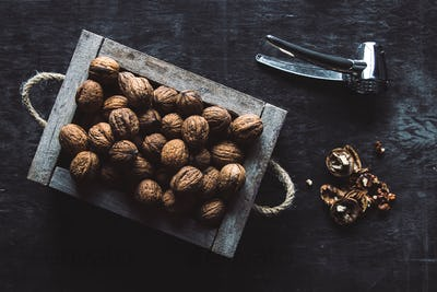 Box with tasty walnuts and nutcracker on dark wooden table, closeup