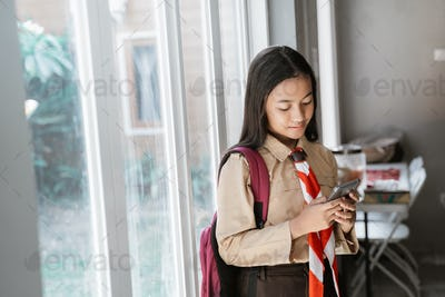 girl wearing scout uniform studying and using mobile phone