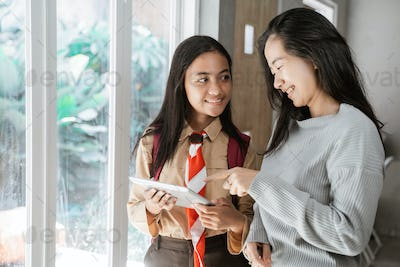 mother daughter using tablet together at home