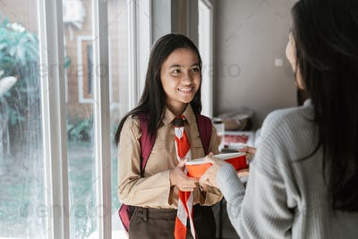 mother help preparing lunch box to her daughter