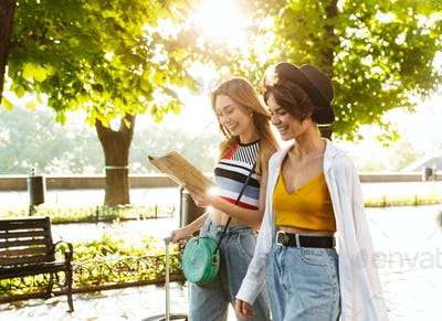 Photo of two cheerful beautiful women holding map while walking