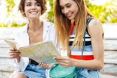 Photo of smiling tourist women holding paper map in green boulevard
