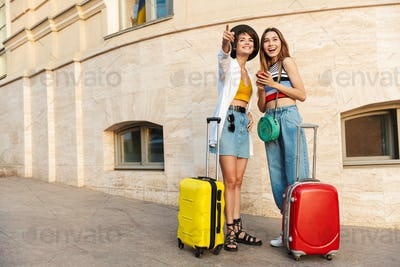 Photo of two cheerful tourist women walking with suitcases on street