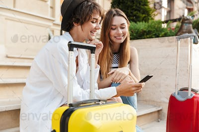 Photo of two laughing beautiful women using mobile phone while sitting