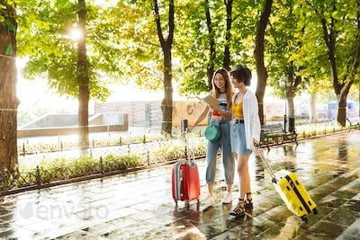 Photo of two joyful beautiful women smiling and holding map while walking