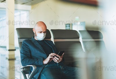 Bald man businessman in medical face mask using mobile phone at airport