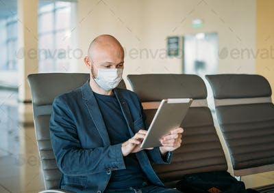 Bald man businessman in medical face mask using tablet at airport