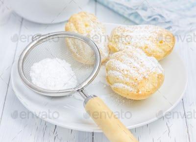 Sugar powdered madeleines on the white plate