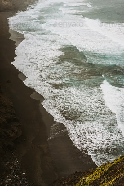 Rough swash waves pounding bluff steep volcanic shore. Trekking trail between Ponto do Sol and