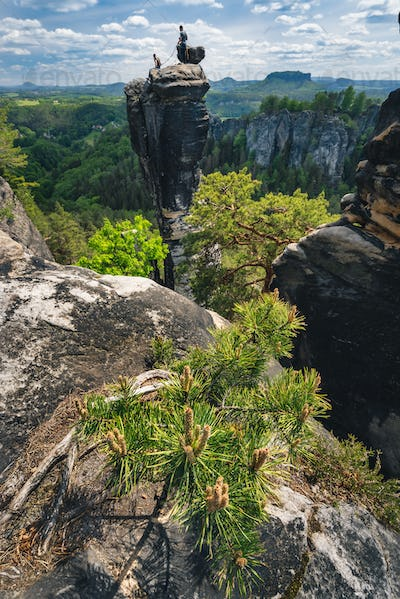 Unrecognized silhouette of climbers with the rope on mountain top in famous Bastei rock formation of