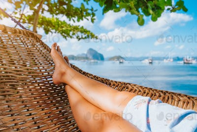 Feet of adult woman relaxing in a hammock on the beach during summer holiday in El nido, Palawan