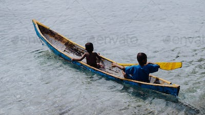 Silhouette of two local boys in a boat on Arborek Island in Raja Ampat, West Papua, Indonesia, near
