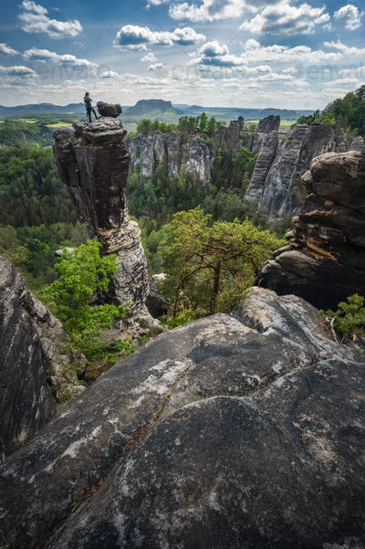 Unrecognized silhouette climber on mountain top enjoying famous Bastei rock formation of national