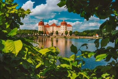 Germany. Castle Moritzburg in Saxony near Dresden in warm day light. Framed by spring lush foliage