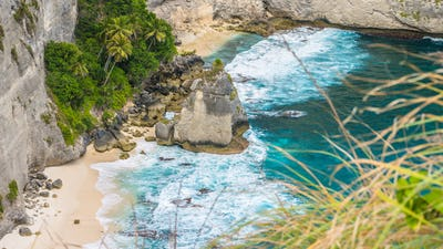 Rock in the ocean with beautiful palms behind at Atuh beach on Nusa Penida island, Indonesia