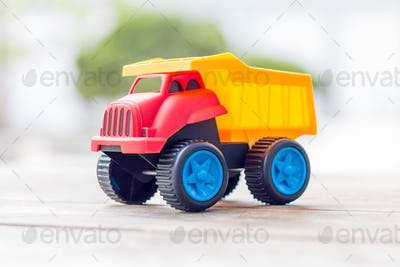 Plastic toy truck on a wooden background