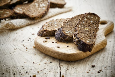 Rye bread slice on a wooden background.