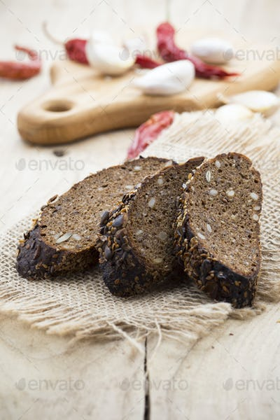 Rye bread slice and chilli pepper, garlic, on a wooden background.