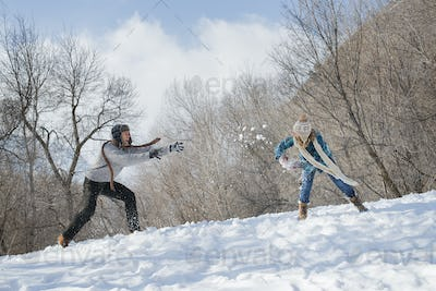 Winter scenery with snow on the ground. A couple having a snowball fight.