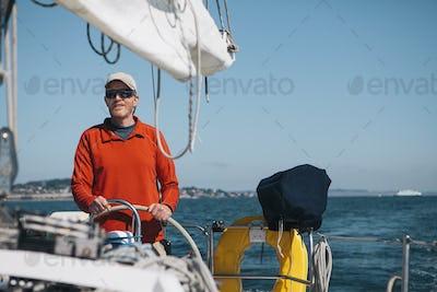 Middle aged man steering sailboat on Puget Sound, Washington, USA