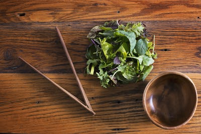 A small round polished wooden bowl and chopsticks with mixed salad leaves.