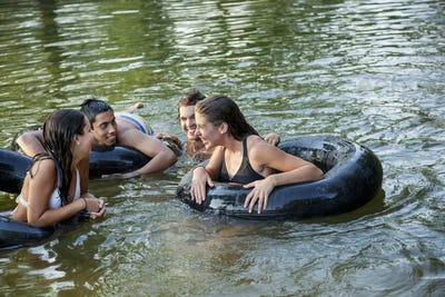 A group of young people, boys and girls, swimming and floating using swim floats and inflated tyres.