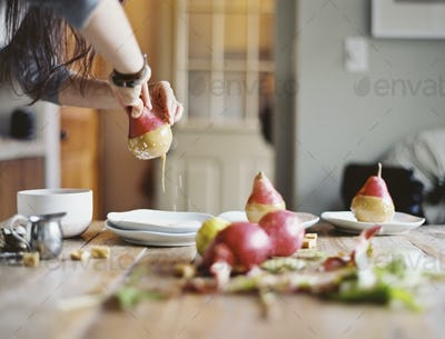 A woman in a domestic kitchen cooking. Dipping fresh organic pears into a sauce for dessert.