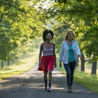 Two women walking down a path lined with trees.