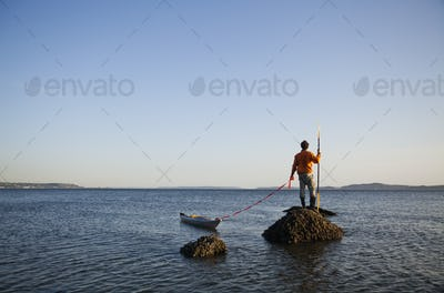 A sea kayaker stands on a rock in the Puget Sound, Washington, USA.