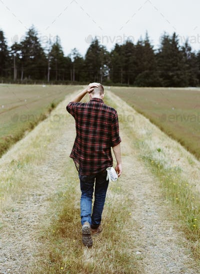 A young man walking through fields on a cranberry farm.