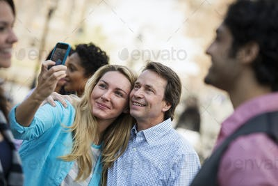 People outdoors in the city. A using her cell phone to take a selfie.