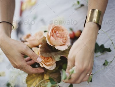 A woman arranging fresh flowers on a tabletop covered with a white cloth. Peach coloured roses.