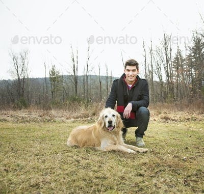 A man in the open air, on a winter day.  Stroking a golden retriever dog.