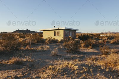 A small abandoned building in the Mojave desert landscape.