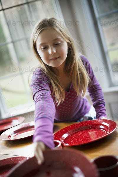 A family home. A young girl laying the table with plates and bowls for a meal.