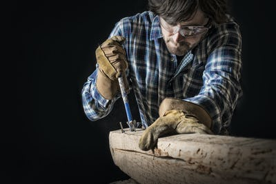 A man working in a reclaimed lumber yard, extracting nails from an old piece of wood.