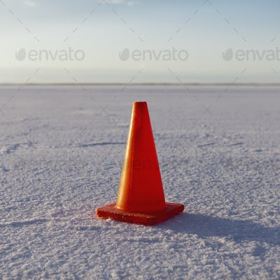 A traffic cone on the Bonneville Salt Flats in the early morning light.