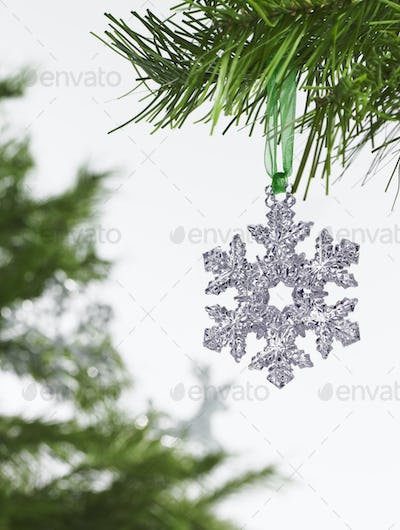 A silver icicle shaped decoration hanging from a pine tree.