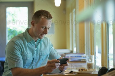A man with short cropped hair sitting at a cafe table, using a smart phone.